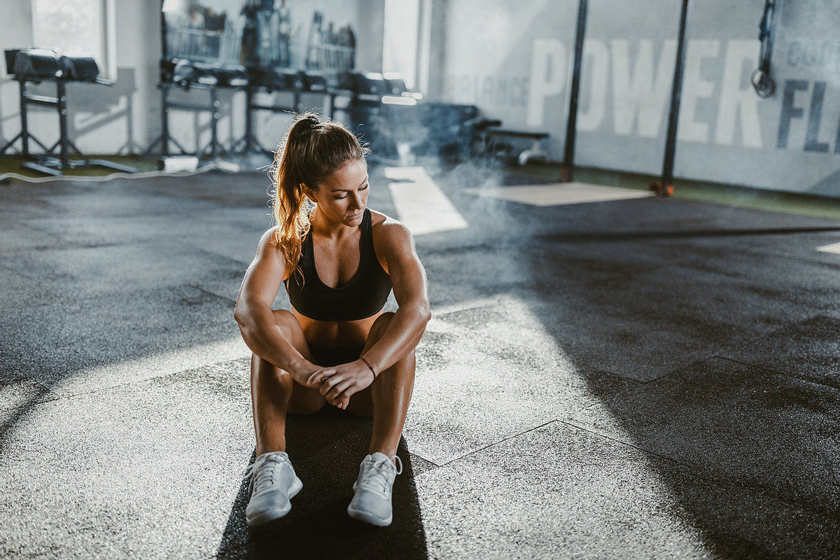 Girl sitting on the floor and recovering from a workout