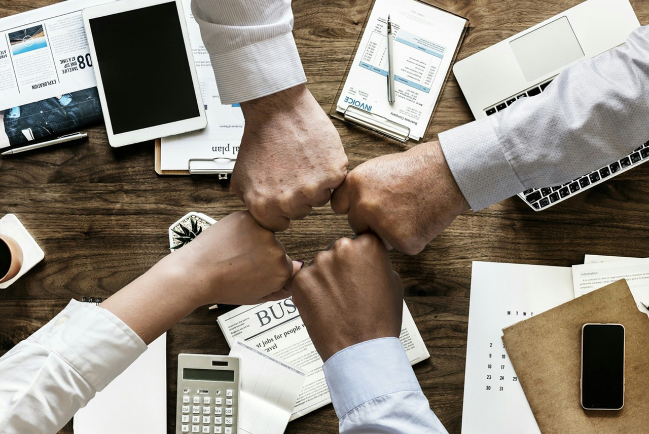 Hands of four coworkers bumping fists together over a messy desk of papers and devices to celebrate their new Tricore Platinum Corporate Wellness Package